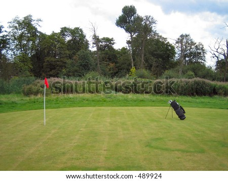 Green on a golf course with bag - stock photo