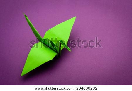 green origami paper crane on purple paper background - stock photo