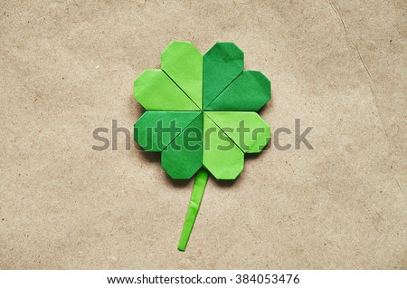 Green origami paper shamrock clover leaf on eco paper background. St. Patrick's Day greeting postcard template. - stock photo