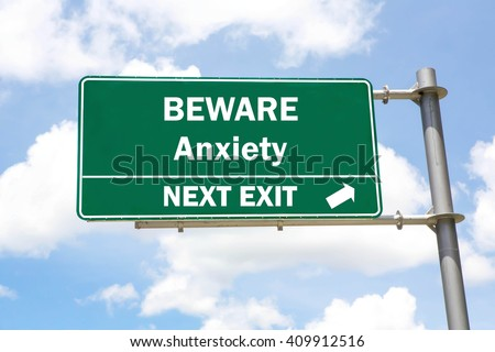 Green overhead road sign with a Beware Anxiety Next Exit concept against a partly cloudy sky background. - stock photo