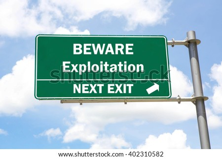 Green overhead road sign with a Beware Exploitation Next Exit concept against a partly cloudy sky background. - stock photo
