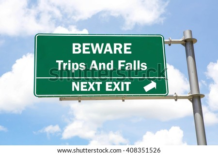 Green overhead road sign with a Beware of Trips And Falls Next Exit concept against a partly cloudy sky background. - stock photo