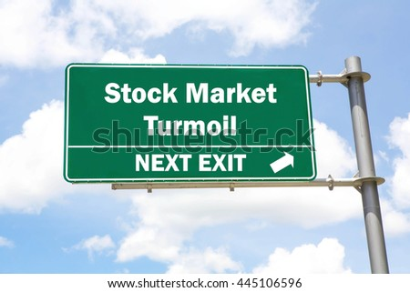Green overhead road sign with a Stock Market Turmoil Next Exit concept against a partly cloudy sky background. - stock photo