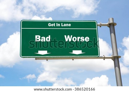 Green overhead road sign with the instruction to get in lane with a Bad or Worse concept against a partly cloudy sky background. - stock photo