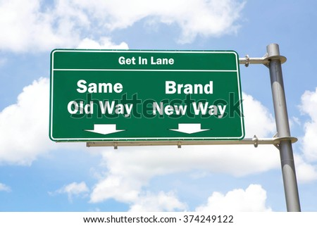 Green overhead road sign with the instruction to get in lane with a Same Old Way or Brand New Way concept against a partly cloudy sky background. - stock photo