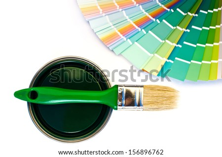 Green paint and swatch. Samples with different shades of green and can of green paint with a brush. Focus on the can. Isolated on white background. - stock photo