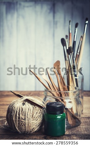 Green paint with art and craft tools on wooden background. Toned. - stock photo