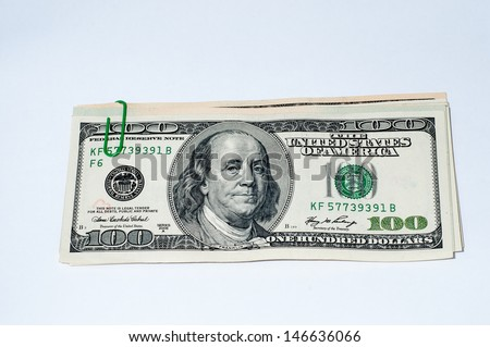 green paper clip with dollars on a white background