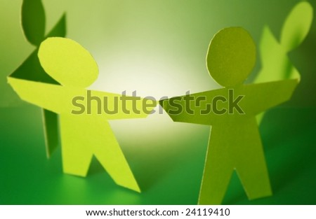 green paper cutouts holding hands - stock photo