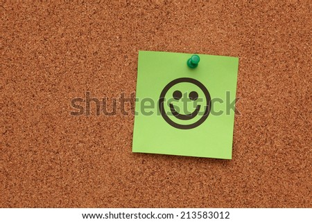 Green paper with smiling face on corkboard (bulletin board). - stock photo