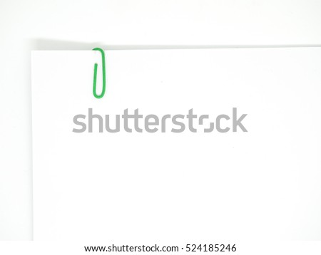 Green paperclip attached on white paper isolated on white background