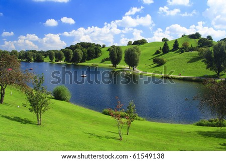 Green park with lake and blue sky in German - stock photo