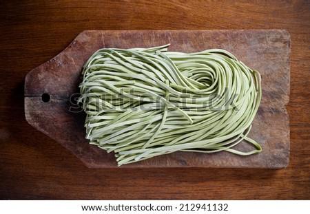 Green pasta on wooden table. - stock photo