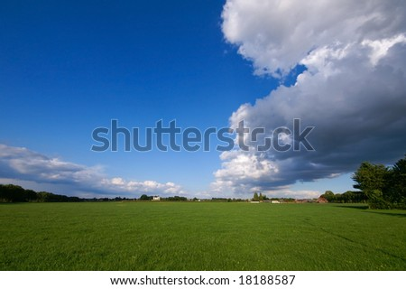 green pasture with big thundercloud overcast
