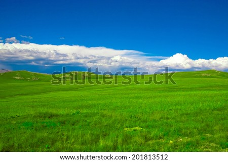 Green pastures in the highlands landscape - stock photo