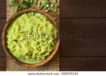 Green pea and parsley dip or spread in wooden bowl, photographed overhead on dark wood with natural light (Selective Focus, Focus on the top of the dip)