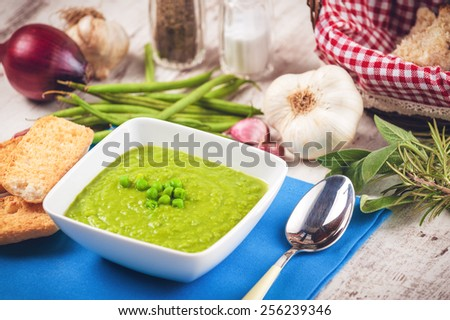 Green pea soup and bread on a blue tablecloth - stock photo
