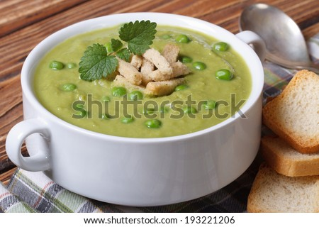 Green pea soup with croutons and mint closeup on a wooden table. horizontal  - stock photo