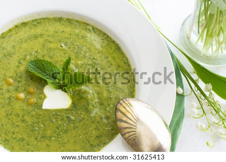 Green pea soup with mint and sour cream - stock photo