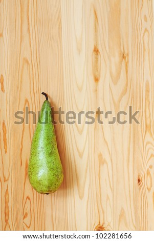 Green pear on a light wood. View from the top - stock photo