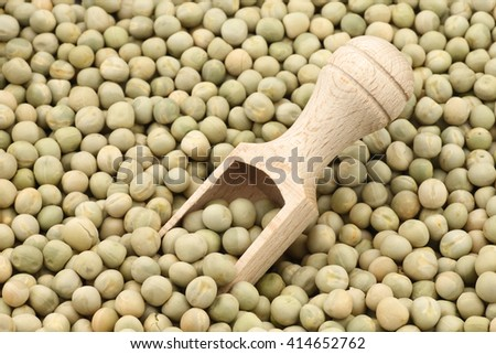 Green peas and wooden scoop background - stock photo