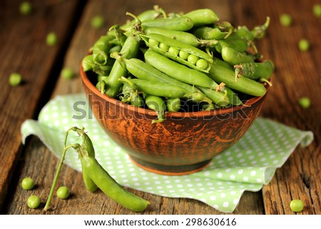 Green peas in a clay bowl on a wooden background - stock photo
