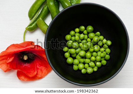 Green peas in black bowl on white wooden background with red poppy flower - stock photo