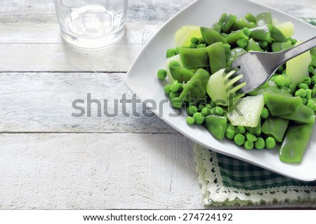 Green peas in white plate on white wooden table in a rustic kitchen.