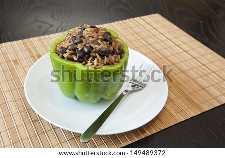 Green pepper stuffed with rice and black beans on a bamboo matt - stock photo