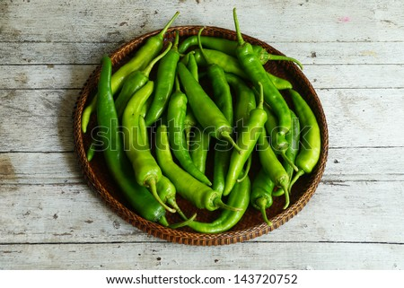 Green peppers in the threshing basket on wooden table - stock photo
