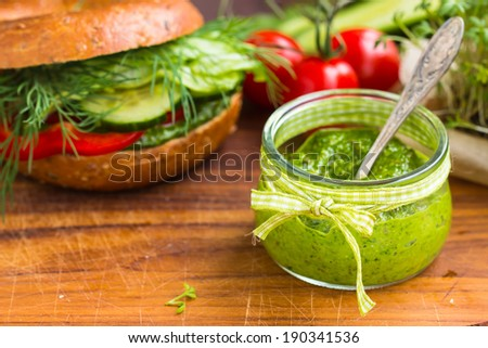 Green pesto in little jar. Vegan bagel and raw vegetables in the background. Selective focus.  - stock photo