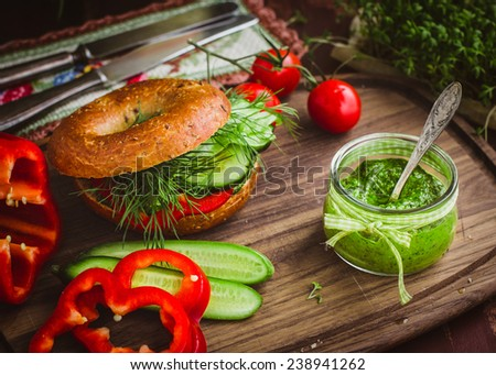 Green pesto, vegan bagel and fresh vegetables on wooden board. Selective focus - stock photo
