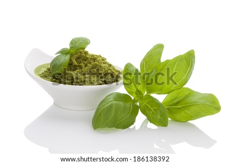 Green pesto with fresh basil herbs in white bowl isolated on white background. Culinary mediterranean eating. - stock photo