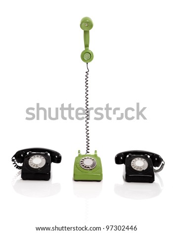 Green phone ringing in the midle of two black phones, isolated on white background - stock photo
