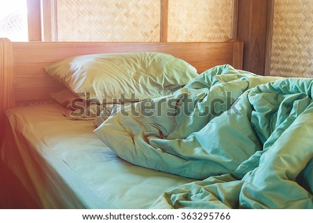 green pillow and blanket with wrinkle messy on bed in vintage wooden bedroom with lighting upper left side, from sleeping in a long night winter. - stock photo