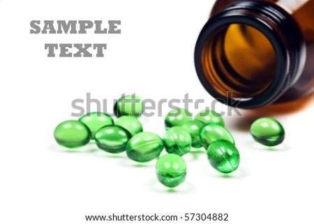 Green pills with pill bottle on a white background with space for text - stock photo