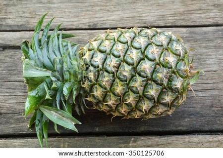 green pineapple fruit on wood plank