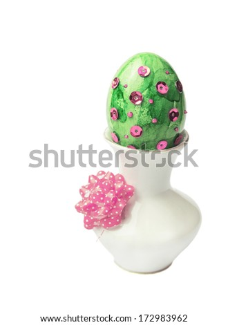 green pink Easter egg with sequins in vase white background