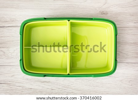 Green plastic box for food storage on the wooden background. - stock photo