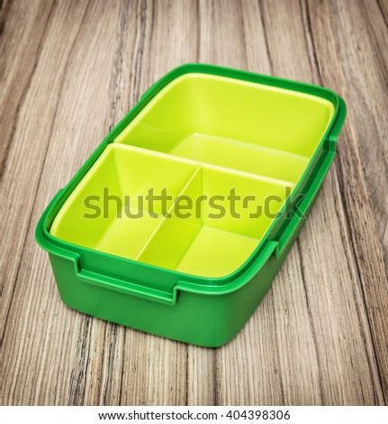 Green plastic box for food storage on the wooden background. Kitchen utensil. - stock photo
