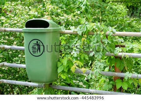 Green plastic dust bin in garden - stock photo