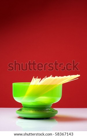 green plastic kitchen scale on a red background with spaghetti