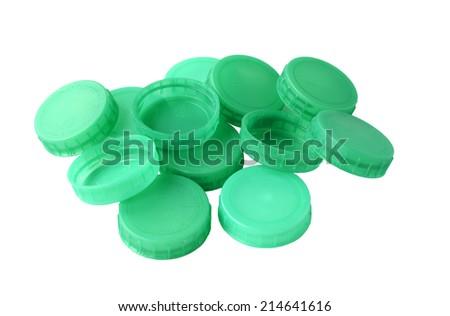 Green plastic milk bottle tops in random pile on white background - stock photo
