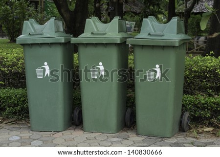 Green plastic recycle bin in park - stock photo