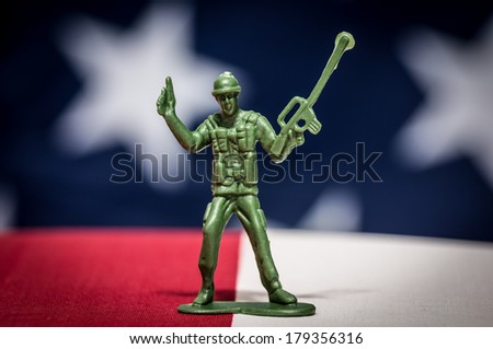 Green plastic soldiers on American flag background with gun - stock photo
