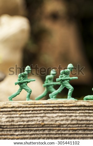 Green plastic toy soldier army unit running on top of an old weathered railway sleeper. Selective focus and wooden textured background  - stock photo