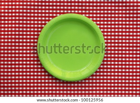 Green plate isolated on red and white checked tablecloth - stock photo