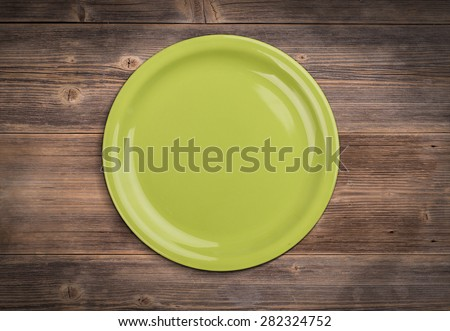 Green plate on vintage wooden board - stock photo