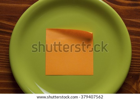 Green plate with blank orange sticky note on wooden background. - stock photo
