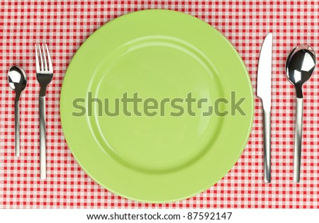 Green plate with cutlery over red tablecloth.